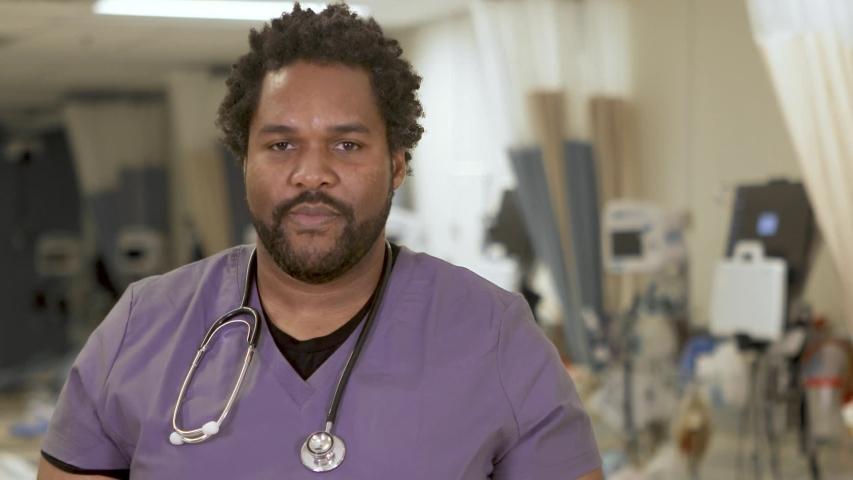 Portrait of a confident black male nurse, close-up in a hospital ward.