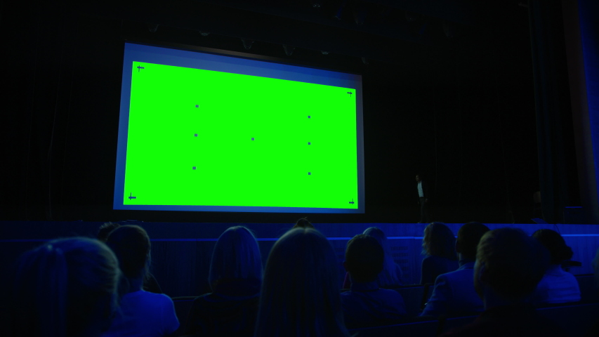 On Stage, Keynote Speaker Presents New Product to the Audience, Behind Him Movie Theater with Green Screen, Mock-up, Chroma Key. Business Live Event or Device Reveal Royalty-Free Stock Footage #1045096429