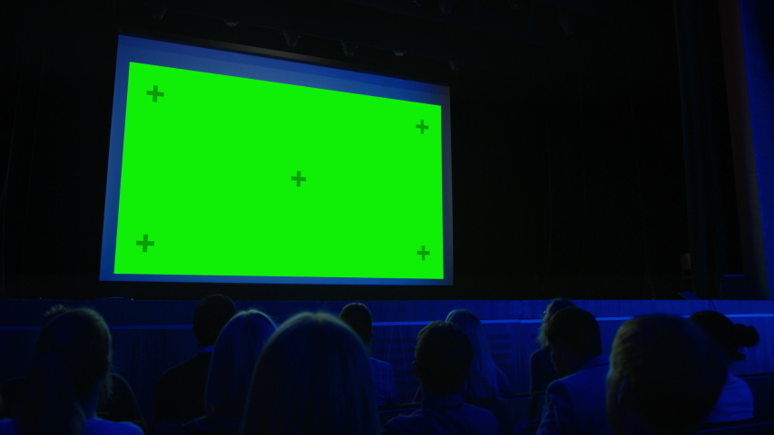 In the Movie Theater Captivated Audience Watching New Blockbuster Film on Mock-up Green Screen. People Watching Video Game Tournament Streaming, Live Concert Video, New Product Release Trailer