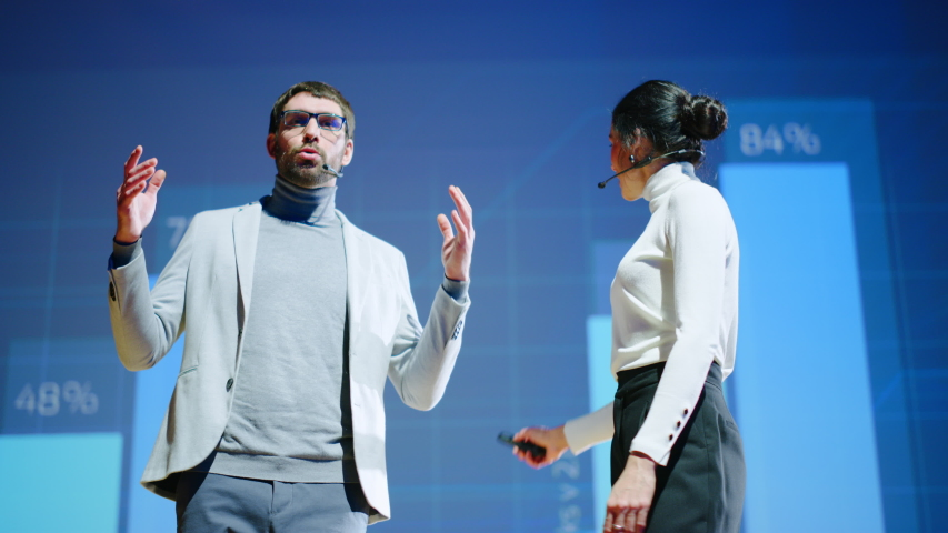 On Stage, Successful Female Executive and Male Manager Present New Product, Show Infographics, Statistics on Big Screen, Talk About Growth. Live Event, Tech Startup, Business Conference | Shutterstock HD Video #1045096594