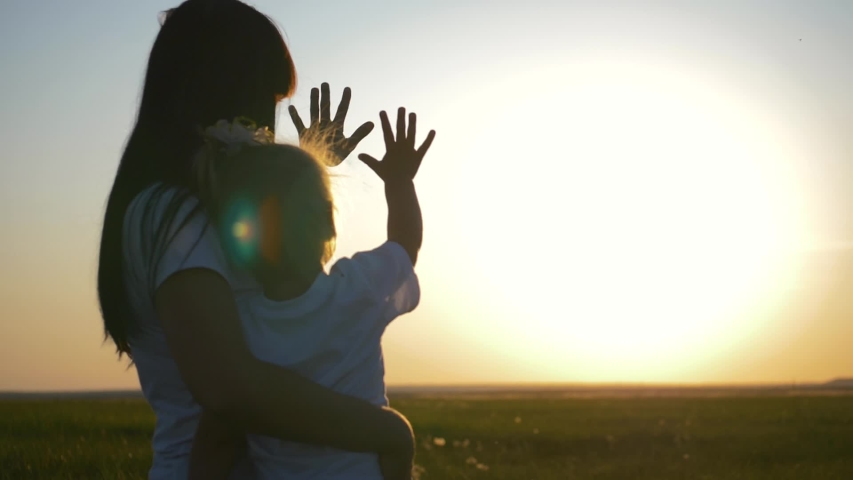 Happy family mom and daughter in a field at sunset. Mom with daughter stretch their hands to the sun while playing with the rays. The concept of a happy family and togetherness with nature
