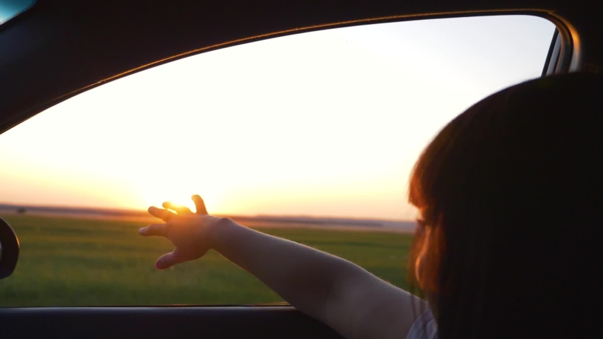 Girl traveling by car. Girl hand in the car window. Sunset in the car window. Girl travel on the road. Silhouette of a hand at sunset. Girl travels on the road by car