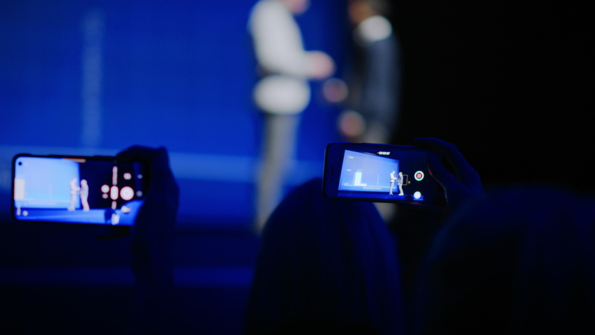 Audience Use Smartphones to Record Two Speakers on Stage Talking on Business Conference. In Audience Hall Public Uses Mobile Phones to Shoot Video of Two Star Presenters, Live Event, Tech Symposium Royalty-Free Stock Footage #1045102513