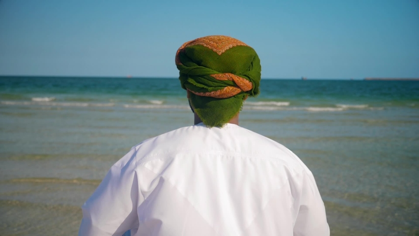 Back view of an Omani man with Oman scarf flag , wearing  omani traditional  dishdasha and  Musaar looking to the sea .