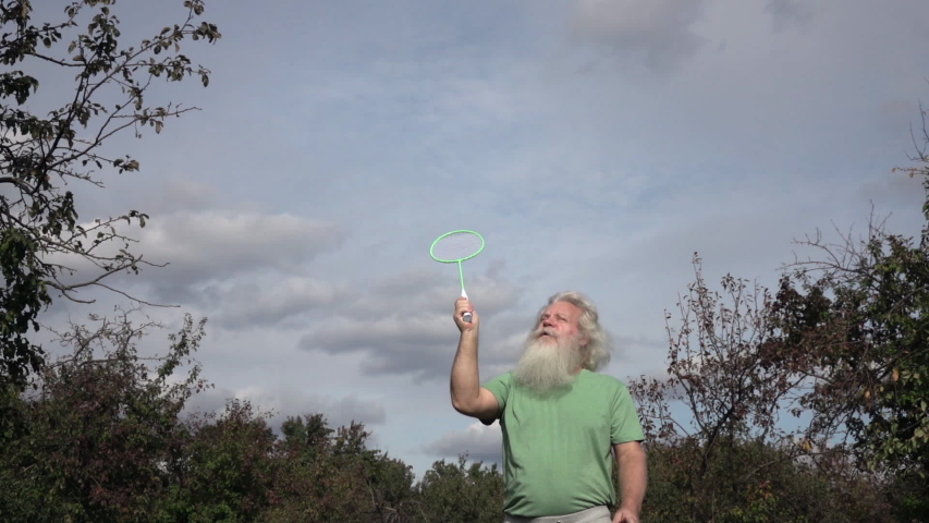 Sportive senior Caucasian man with splendid grey hair and beard is playing badminton. Beautiful portrait of active European people in summer leisure. Outdoor lifestyle scene in slow motion footage.