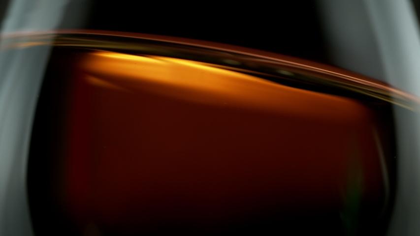 Super slow motion of waving whiskey, cognac or rum in macro shot. Filmed on high speed cinema camera, 1000 fps