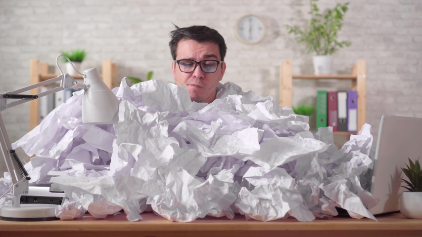 Perplexed man office worker with glasses in a heaps of paper on the office desk