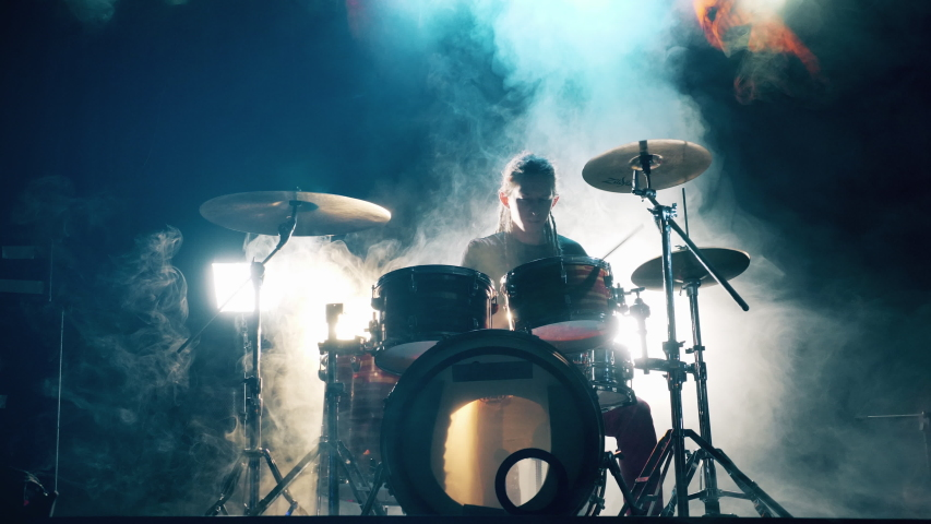 Musician is playing the drum set in the dark clouded studio. Male Drummer playing drums in smoke.