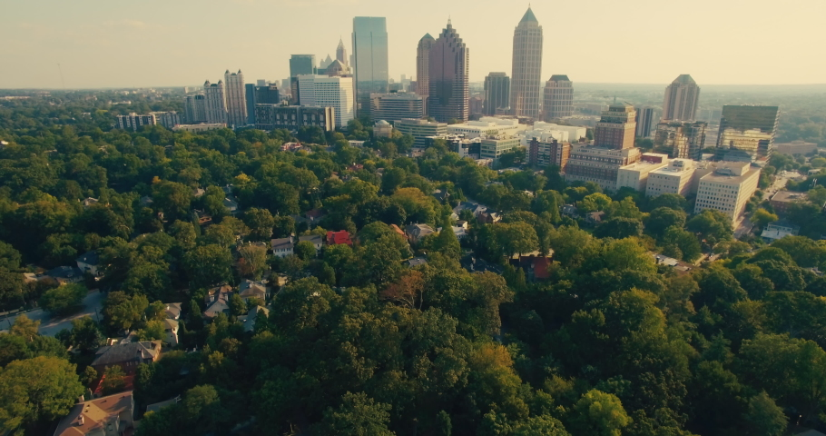 Aerial view of downtown Atlanta, Georgia and suburban neighborhoods in the state capital. Dron shot in a summer sunset featuring a beautiful skyline of Atlanta, Georgia USA.