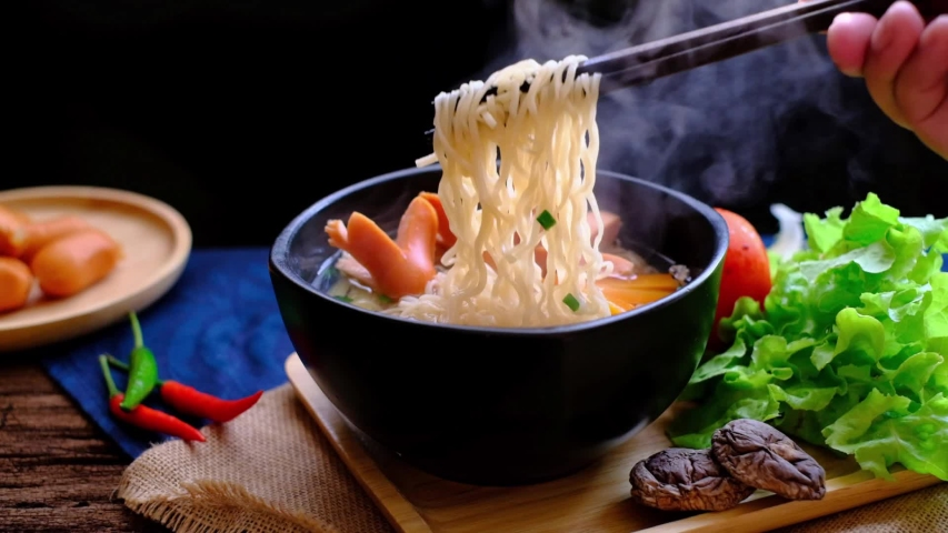 Man's hand pick up steamy instant noodle /hot ramen with chopsticks with ingredients on wood table. Hot ramen is delicious & cheap. Quick meal, instant noodle and cheap Asian steamy food concept.  Royalty-Free Stock Footage #1045145374