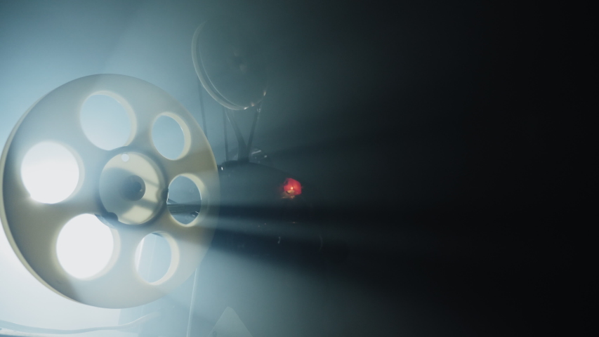 Old 8mm film projector working in the night in a smokey room. Close-up of a reel with a film rotating and light rays. Royalty-Free Stock Footage #1045159684