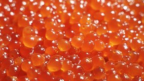 Appetizing background of red caviar. Salmon or trout caviar is laid out in a plate and rotates