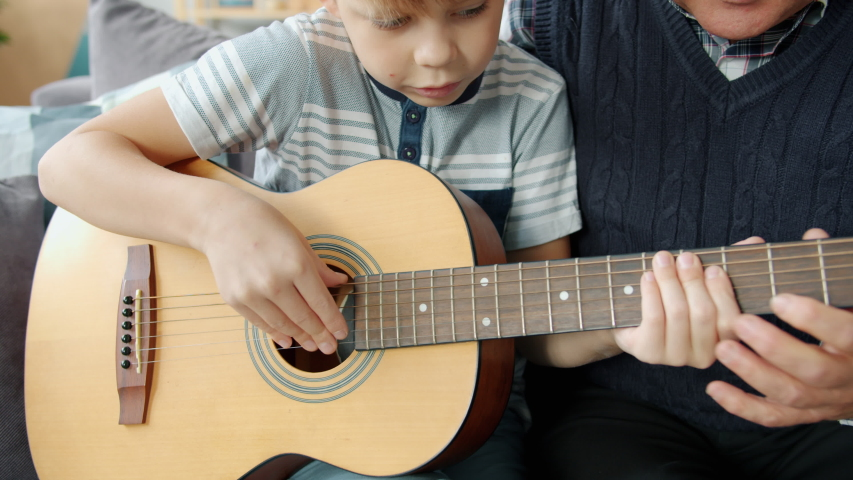 Caring grandfather is helping cute kid teaching guitar playing at home together enjoying domestic music lesson. People and musical education concept.