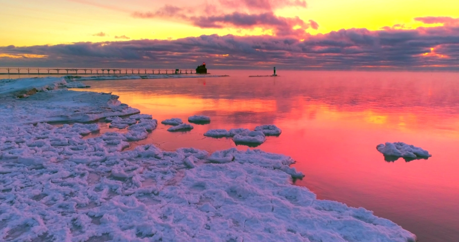 Icy red waters reflecting the Winter twilight sky, with lighthouse, moving aerial view. The colors are unaltered, exactly as my cameras recorded them. Lake Michigan sunrises can be intense.