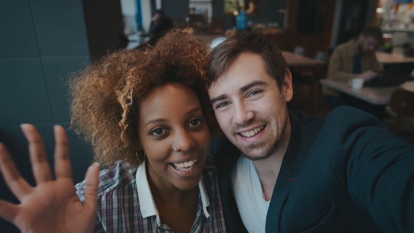 POV shot of multiracial young couple making video call sitting in modern cafe on date. African girl and caucasian guy talking on video call and waving hands. Cute couple making selfie