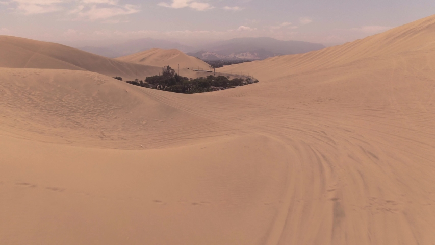 Sandy desert oasis lake. DRONE. Water in middle of hot sand desert. Romantic, holiday, couple, honeymoon, scenic shot, with sand and footprints. Tourism shot in Huacachina, Peru. Epic, dramatic shot.