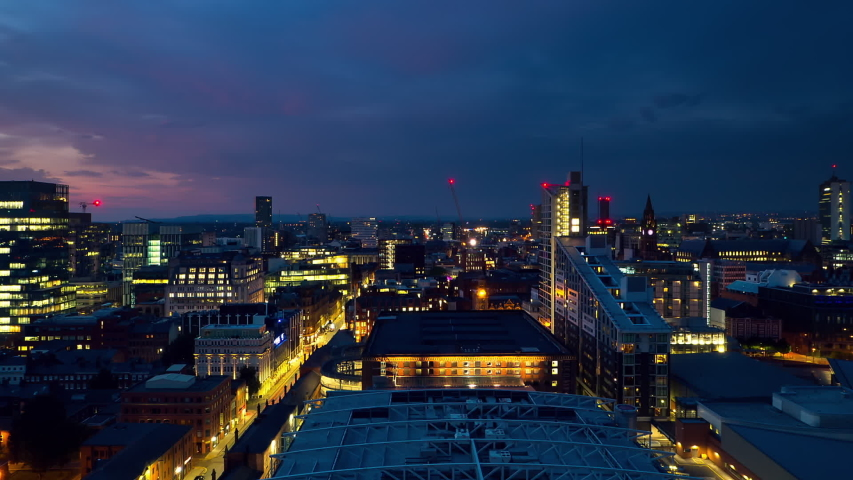 Manchester city time lapse sunset to night aerial panoramic view england uk zoom out