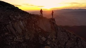 Aerial 4k drone clip with couple of hikers watching a beautiful sunset on top of Bucegi mountain ridge, during magical golden hour light in autumn season, in Romania