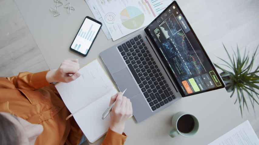 Timelapse top shot of female investment analyst sitting at desk in office, writing in notebook, using smartphone, analyzing diagrams and graphs and typing on laptop with currency trading software Royalty-Free Stock Footage #1045209418