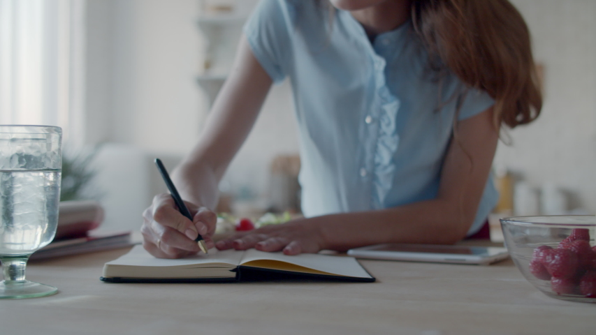 Close up of young businesswoman making notes in notebook at home office. Smiling girl planning at home desk in white kitchen interior. Closeup woman hand writing in diary in slow motion. Royalty-Free Stock Footage #1045212235