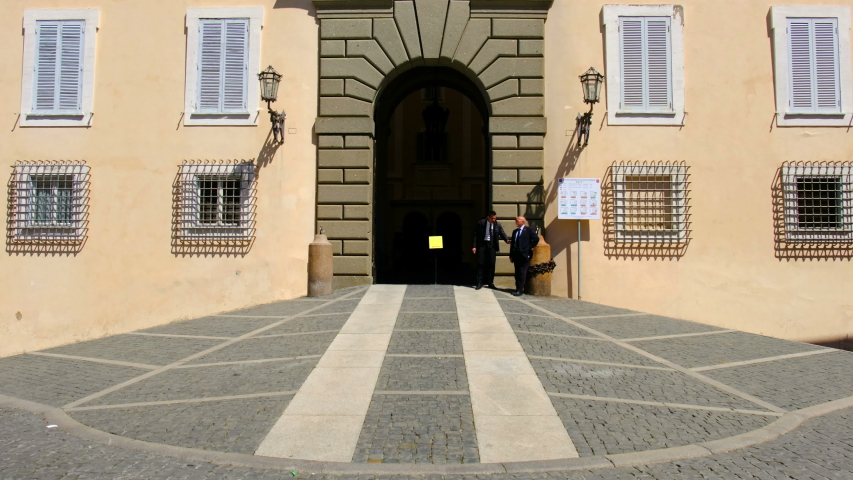 Rome province local landmark of Castel Gandolfo in Lazio region of Italy. entrance of Palazzo Pontificio building with elegant guards chatting in Castel Gandolfo, Italy, 04 May 2019