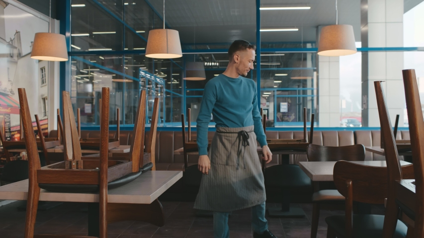 Young waiter or cafeteria owner putting chairs on tables to clean area at the end of workday. Male restaurant owner preparing in for opening. Small business and startup concept