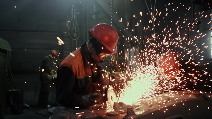 Manufacture of Railcar or Carriage, Train Wagon Production, Factory Workers are Welding in Protective Helmets and Glasses, Beautiful Epic Shot, Dolly Out, Slow Motion