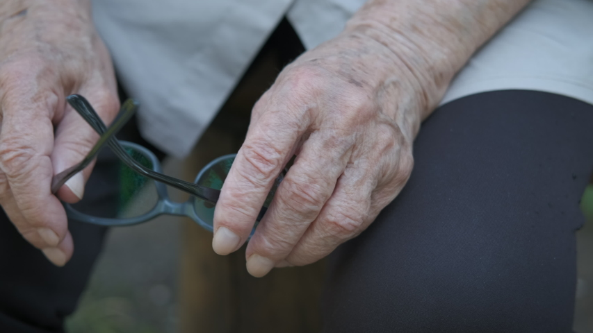 Hands of an elderly person. Hands of an old man with glasses for vision.