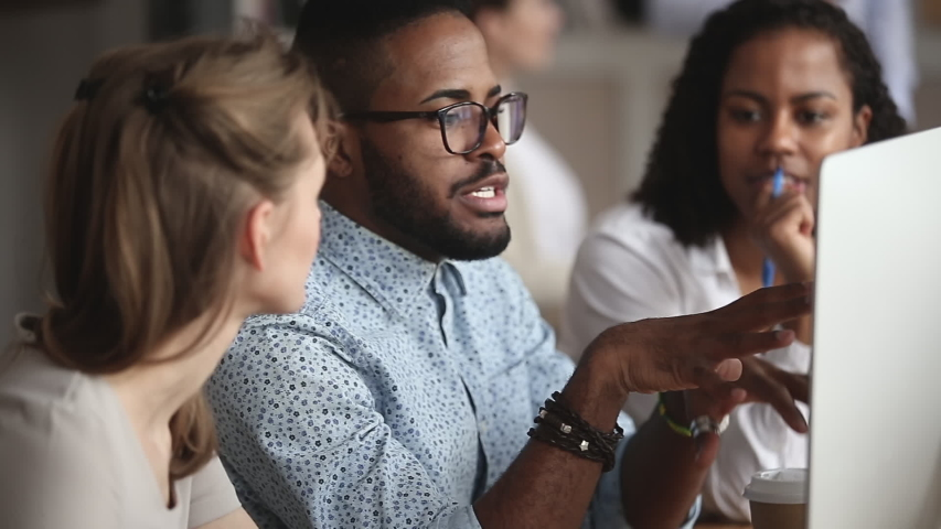 Confident smart african american manager in eyeglasses explaining corporate software details to motivated mixed race female colleagues. Smiling multiracial employees listening to leader instructions. Royalty-Free Stock Footage #1045279321
