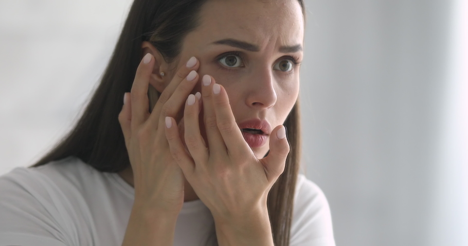 Worried young woman looking in mirror, examining wrinkles in eyes area. Unhappy millennial lady dissatisfied with skin condition, thinking of professional skincare products or cosmetologist meeting. | Shutterstock HD Video #1045279339
