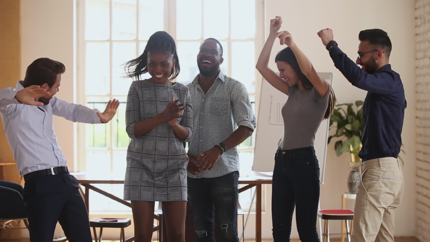 Happy diverse business people dancing at office, celebrating corporate achievement. Overjoyed young mixed race international company staff having fun, enjoying Friday party together at workplace.