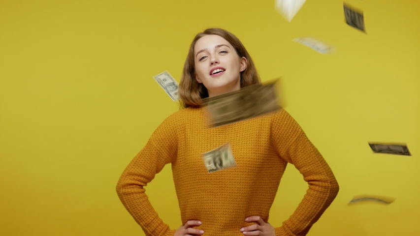 Confident rich girl in casual outfit looking arrogantly at camera while dollar bills falling around. proud of big money and wealthy life, sudden lottery gain. studio shot isolated on yellow background   Shutterstock HD Video #1045280308