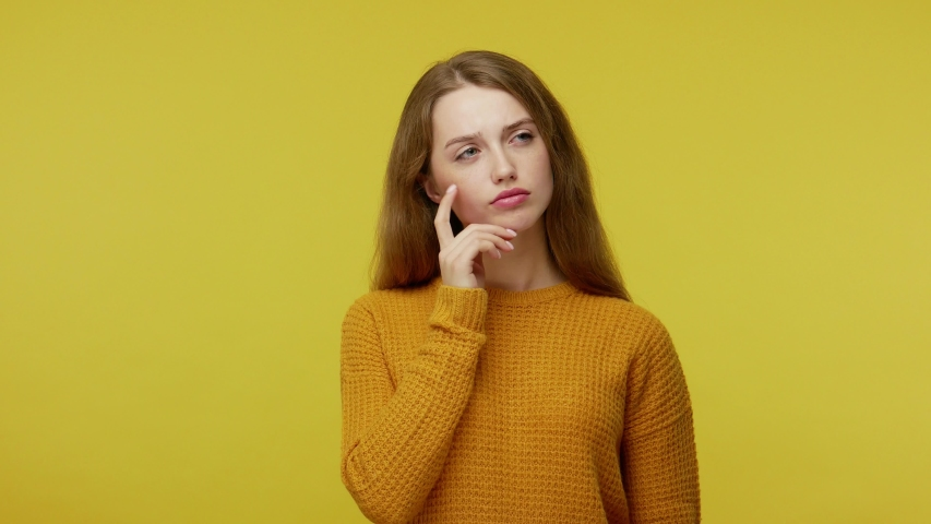 Thoughtful pretty girl with brown hair in pullover rubbing her chin and looking aside with pensive expression. pondering a solution, doubting question. indoor studio shot isolated on yellow background