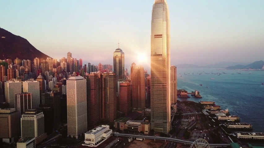 Aerial morning view of Hong Kong city skyline. A beautiful morning sunrise by Victoria Harbour in Hong Kong City, China. Small boats are passing by in the bay. Timelapse. Landmark. Victoria. Harbor.