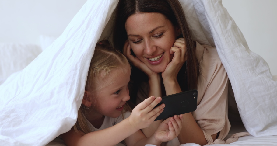 Happy 30s mother lying on bed under duvet with joyful little daughter, small kid girl holding cell phone, taking selfie with smiling mommy, using funny mobile apps, having fun together in bedroom. Royalty-Free Stock Footage #1045292032