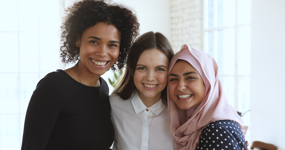 3 cheerful friendly diverse millennial women bonding laughing looking at camera, three happy young ladies having fun embracing in office, closeup portrait, multicultural unity friendship concept