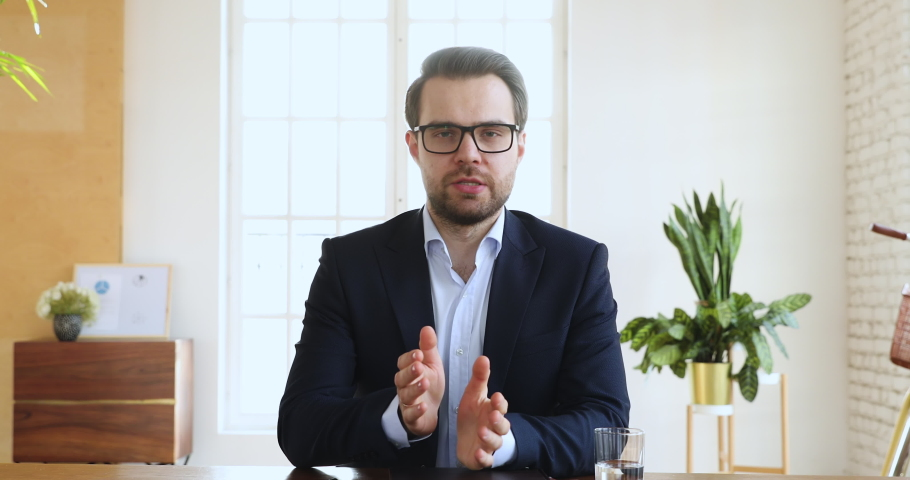 Confident businessman ceo wear suit speaking looking at camera in office, male executive manager talking make conference online video chat call job interview recording online training, web cam view