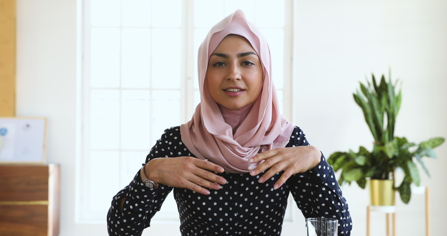 Confident young indian muslim business woman wear hijab speak look at camera, islamic arabic lady talk to webcam make video conference call job interview record webinar online presentation in office