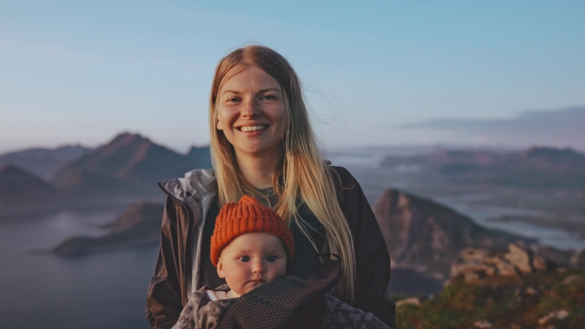 Mother with baby daughter traveling family vacations in Norway hiking together active healthy lifestyle happy smiling woman and child outdoor happy emotions Lofoten islands landscape