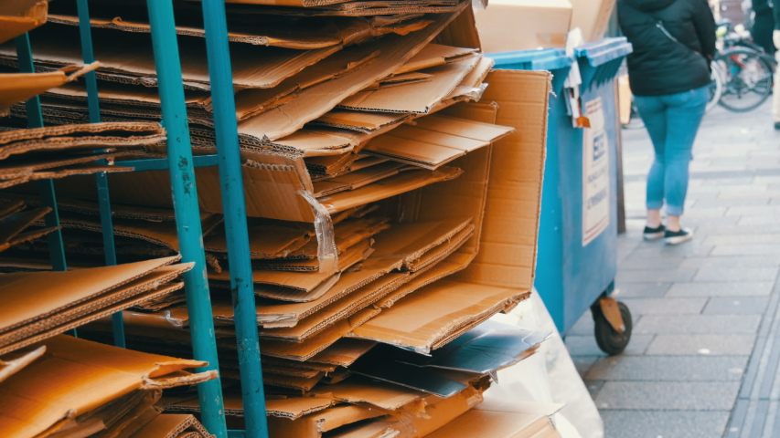 Cardboard boxes folded for further processing. Garbage sorting, environmental protection. | Shutterstock HD Video #1045312294