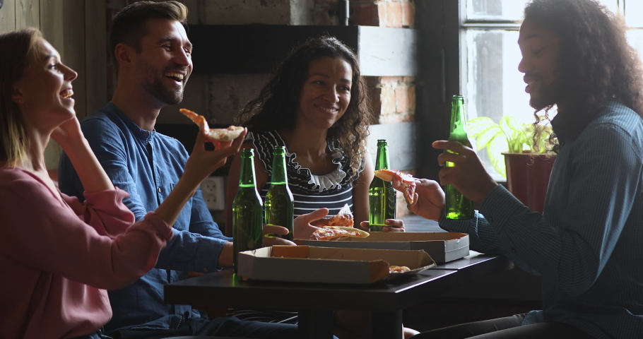 Happy african american guy holding bottle of beer and pizza slice, telling funny joke storytelling to laughing multiracial friends. Excited mixed race people enjoying conversation while sharing lunch.