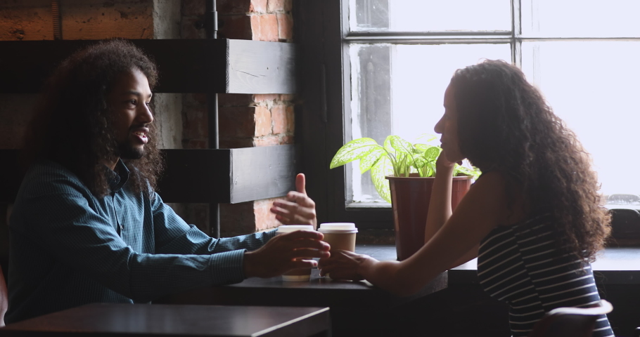 Young african american man and woman sitting in front of each other at wooden table, chatting in cafe. Millennial mixed race friends interacting communicating talking sharing news at meeting.