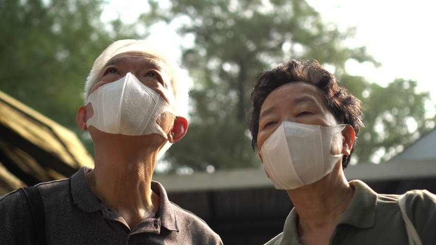 Hopeless Asian Chinese elder couple aware of 2019 ncv outbreak and smog situation wear preventing mask | Shutterstock HD Video #1045331554
