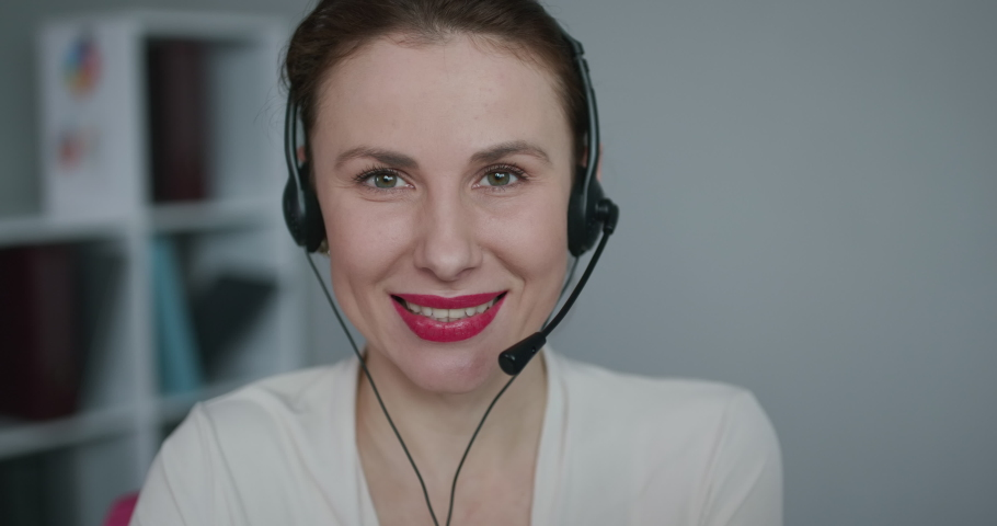 Attractive young female customer service agent talking to a customer with a telephony headset as she looks at the camera.