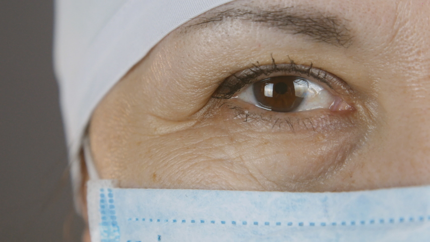 Closeup portrait of experienced caucasian female surgeon, doctor with mask ready to work in a hospital or clinic. Eyes of a doctor | Shutterstock HD Video #1045356877