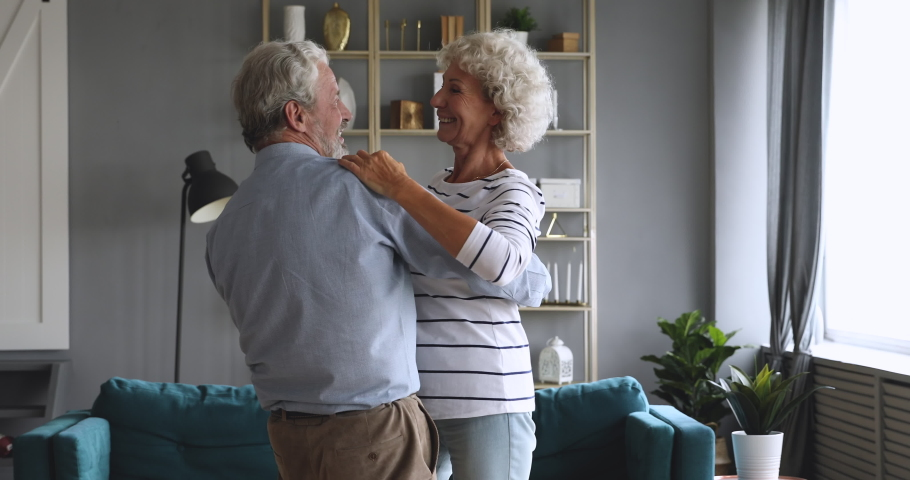 Happy carefree elderly senior grandparents dancing waltz in modern living room, loving old husband laughing holding mature wife enjoying retirement lifestyle talking in slow dance having fun at home Royalty-Free Stock Footage #1045379170