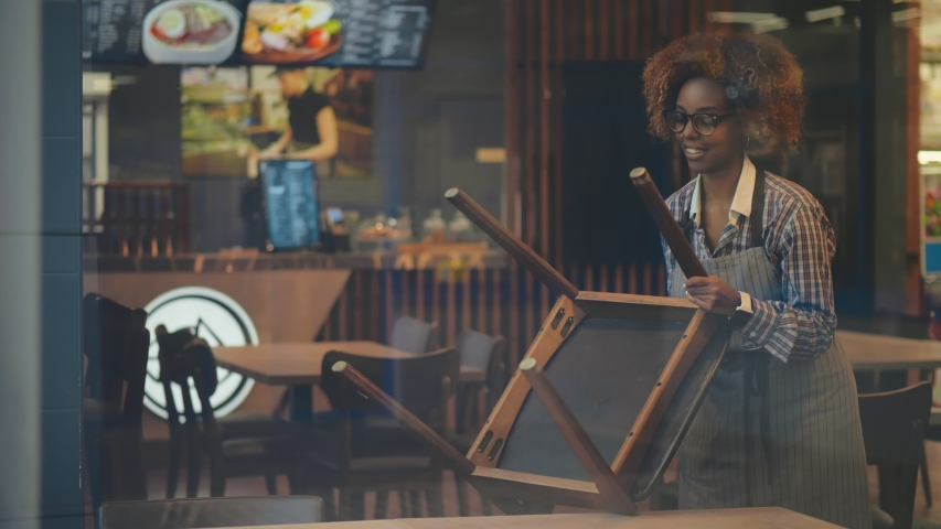 Portrait of beautiful afro-american waitress in apron putting chairs on table preparing cafe for opening. Waiting staff cleaning restaurant. Small business and food service concept. | Shutterstock HD Video #1045390894