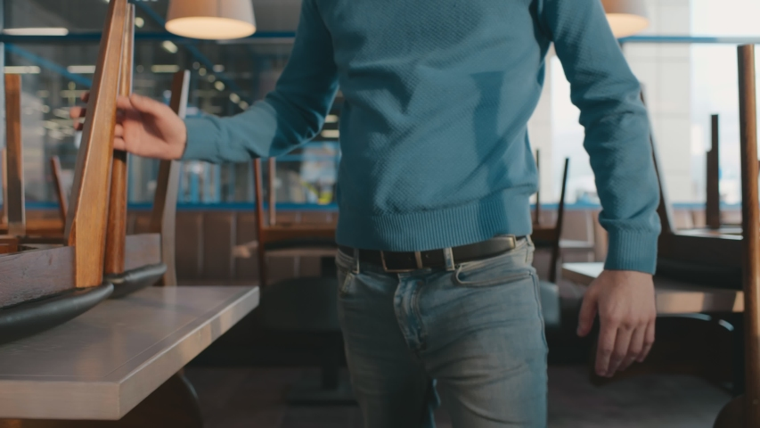 Portrait of young male cafe owner inspecting furniture and cleanliness of dining area before opening. Elegant man walking among tables in empty restaurant. Small business and food service concept