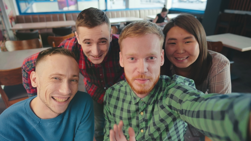 Happy diverse multi racial group of young students having a video chat, as seen from the point of view POV of the smartphone camera. Positive friends have fun at fast food cafe