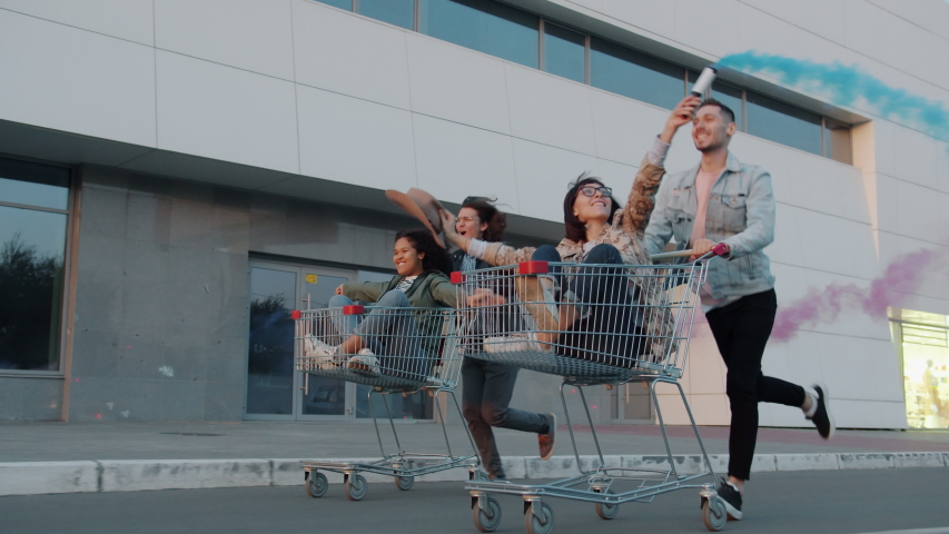 Cheerful youth men and women are riding shopping carts in city street holding smoke flares laughing enjoying leisure time. Freedom and friendship concept.